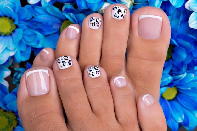 Lindas unhas femininas das pernas com bela manicure francesa e design de arte