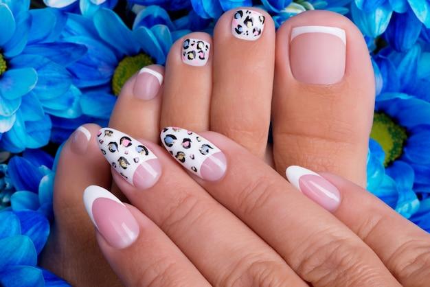 Lindas unhas femininas de mãos e pernas com bela manicure francesa e design artístico