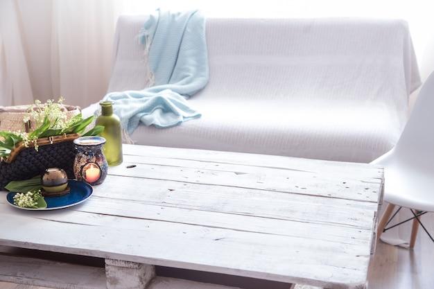 Lindas velas acesas com folhas verdes na bolsa na mesa branca