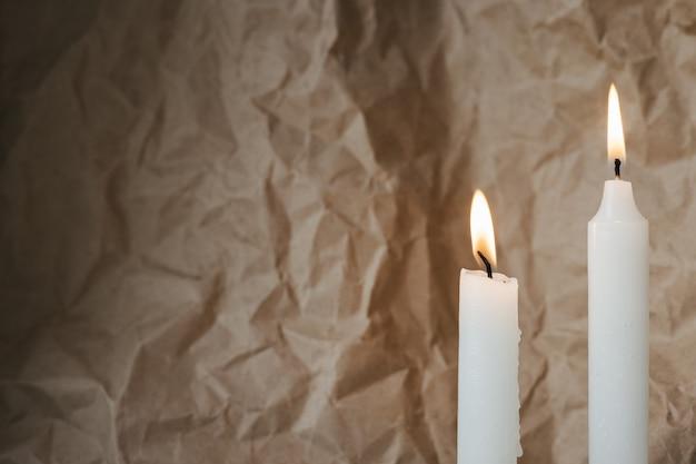 Lindas velas brancas acesas na mesa contra a vista lateral de papel artesanal