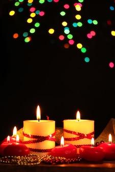 Lindas velas na mesa de madeira no fundo brilhante