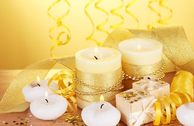 Lindas velas, presentes e decoração em mesa de madeira com fundo amarelo