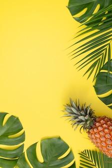 Lindo abacaxi em folhas tropicais palm monstera isoladas em fundo amarelo pastel brilhante, vista superior, plana leiga, sobrecarga acima da fruta de verão.