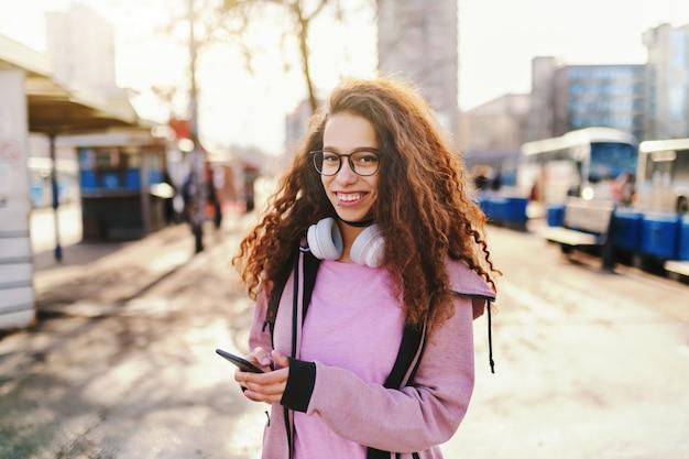 Lindo adolescente com sorriso e fones de ouvido no pescoço, usando o telefone inteligente na rua.
