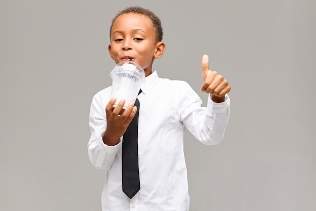Lindo adorável aluno de pele escura vestindo camisa branca e gravata preta fazendo gesto de polegar para cima enquanto toma um milkshake saudável na hora do almoço na escola, com olhar alegre
