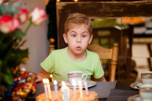 Lindo adorável menino de seis anos na camisa verde, comemorando seu aniversário, soprando velas no bolo caseiro, interior