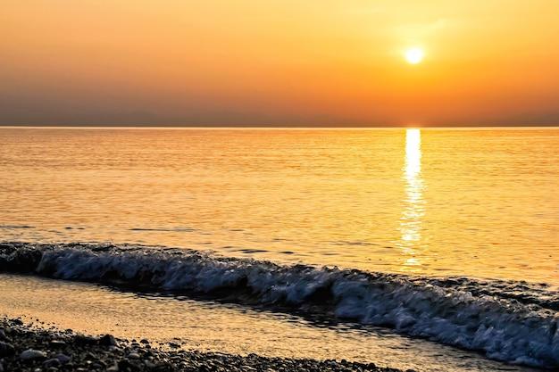 Lindo amanhecer dourado visto da praia em rodes, grécia