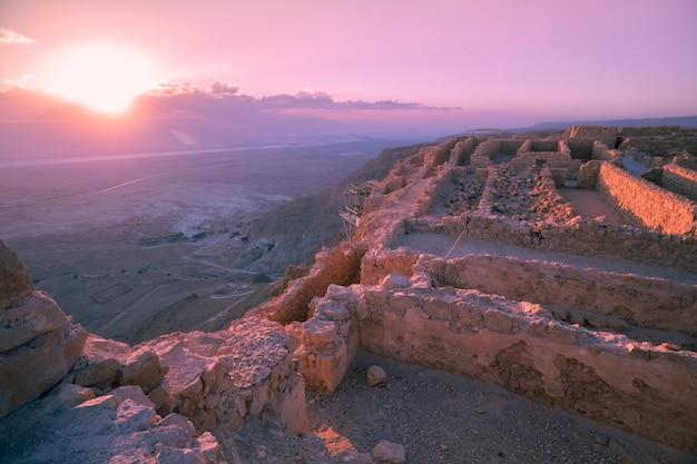 Lindo amanhecer roxo sobre a fortaleza de masada. ruínas do palácio do rei herodes no deserto da judéia