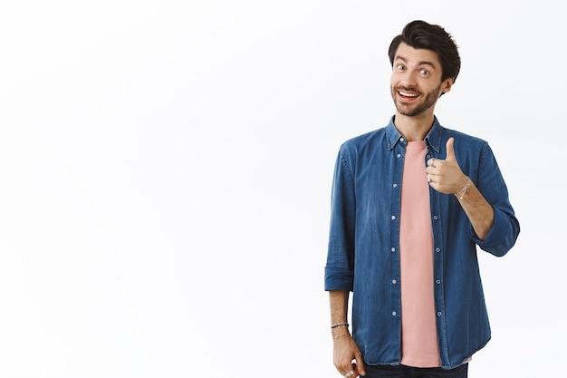 Lindo amigo masculino parabenizá-lo com a promoção, dizendo bem feito e mostrar o polegar para cima em sinal de aprovação. homem barbudo satisfeito torcendo, concorda e gosta do novo produto, recomendo tentar você mesmo Foto Premium