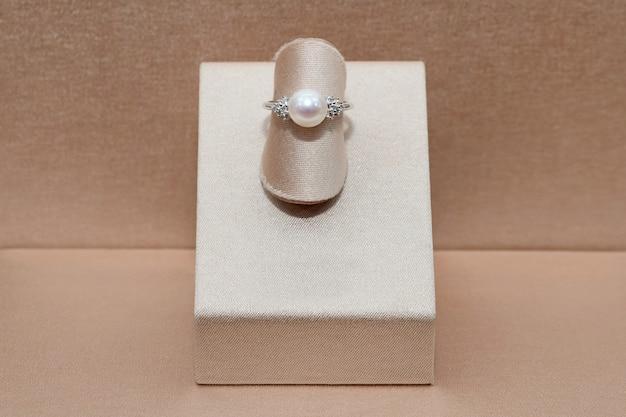 Lindo anel de diamante em ouro com pérola de esfera de brilho exibida em um carrinho. jóias de luxo