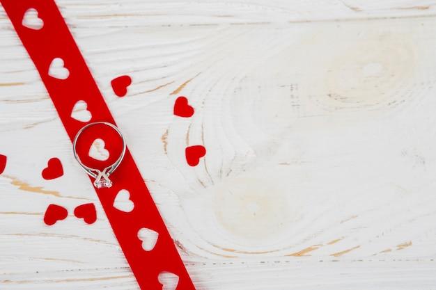 Lindo anel na fita perto de corações de ornamento