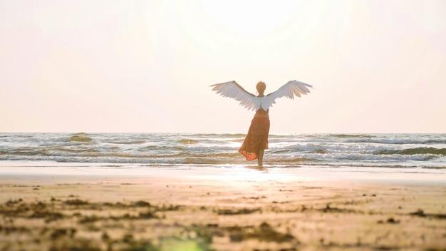 Lindo anjo feminino andando descalço em direção ao mar ao pôr do sol