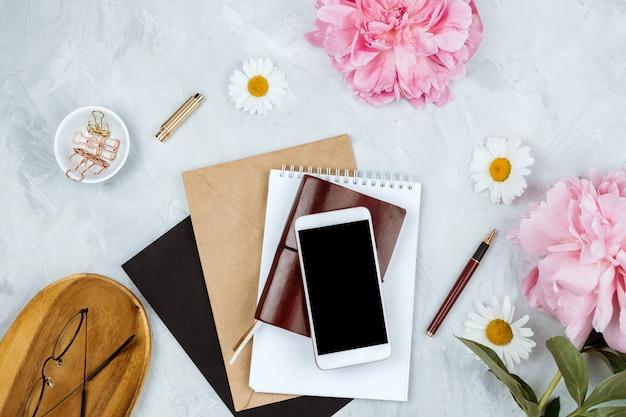 Lindo apartamento feminino colocar maquete com peônias rosa, vários artigos de papelaria e óculos em fundo cinza