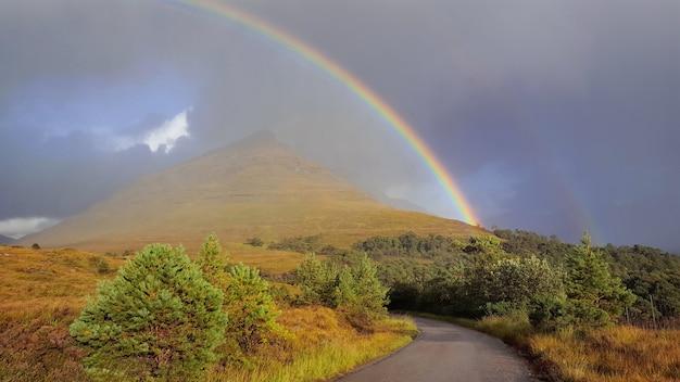Lindo arco-íris no céu dramático sobre uma estrada atravessando terra colorida
