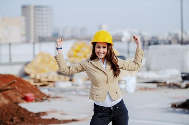 Lindo arquiteto feminino bem sucedido torcendo por excelente trabalho realizado no canteiro de obras.