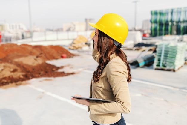 Lindo arquiteto feminino com cabelo castanho, vestido casual inteligente e com capacete na cabeça segurando o tablet em pé no canteiro de obras.