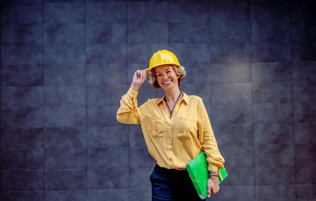 Lindo arquiteto feminino sênior sorridente caucasiano com capacete na cabeça e documentos sob a axila, posando em frente a parede cinza ao ar livre.