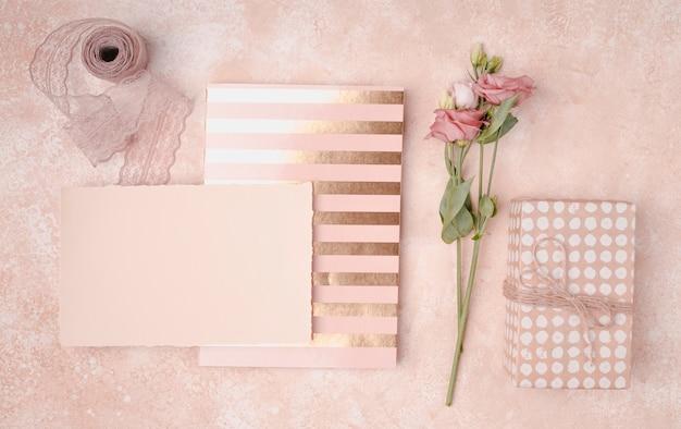 Lindo arranjo com convites de casamento e flores