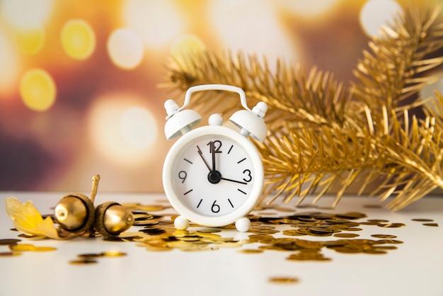 Lindo arranjo com relógio mostrando meia-noite e pinheiros