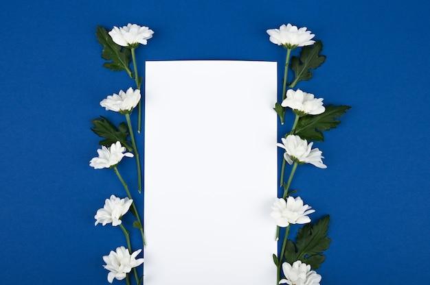 Lindo arranjo floral retangular de flores brancas com um cartão em branco e lugar para texto em um espaço azul. conceito de flores da primavera