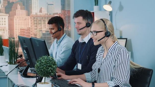 Lindo atendimento ao cliente feminino trabalhando em um call center ocupado, conversando com o cliente internacional