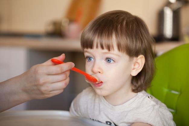 Lindo bebê come mingau da mão da mãe.