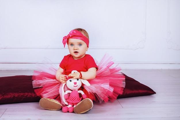 Lindo bebê em uma saia rosa, sentado com um coelho. parentalidade.