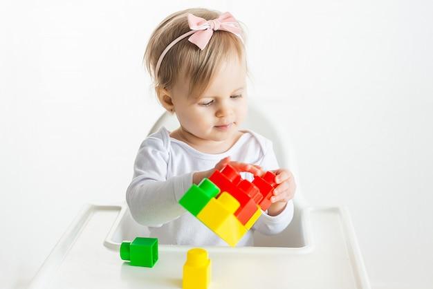 Lindo bebê loiro brinca com um construtor brilhante sobre uma mesa branca. criatividade infantil em quarentena. desenvolvimento precoce de crianças.