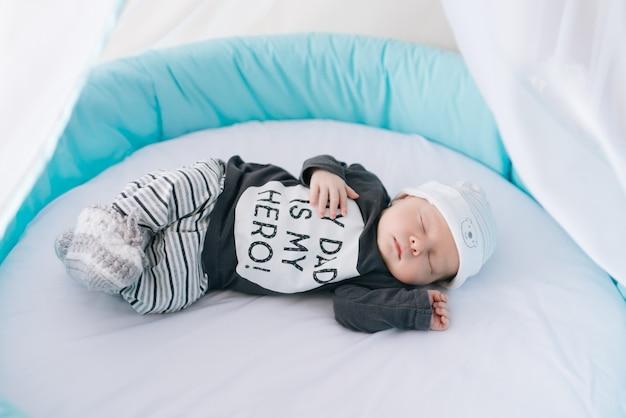 Lindo bebê recém-nascido, deitado em uma cama oval com belos pára-choques em cinza delicado