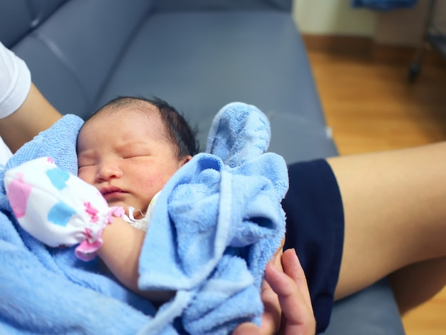 Lindo bebê recém-nascido dormindo nas mãos dos pais.