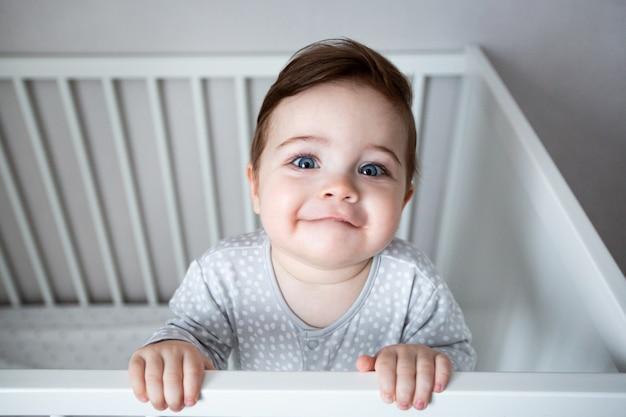 Lindo bebê rindo em pé em uma cama redonda branca.