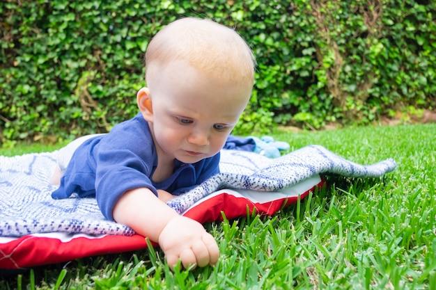 Lindo bebê ruivo com camisa azul tocando a grama no parque e deitado de barriga. linda mãe assistindo infantil no parque e sorrindo. verão em família