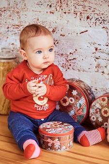 Lindo bebê sentado à mesa segurando uma noz e olhando para o lado