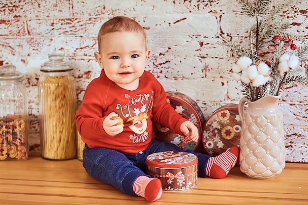 Lindo bebê sentado à mesa segurando uma noz