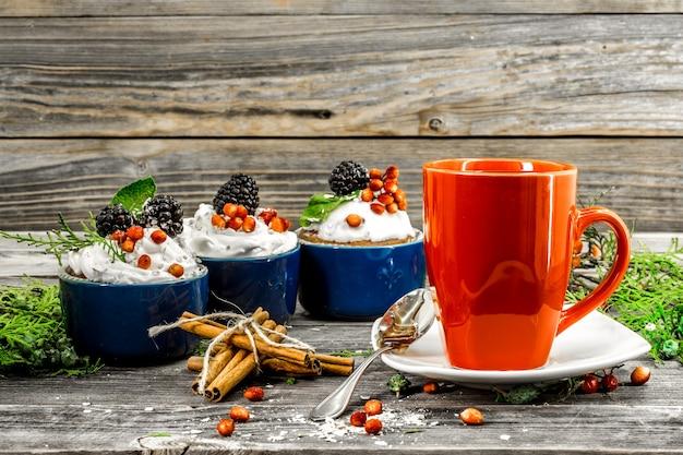 Lindo bolinho de natal com creme e frutas vermelhas na mesa de madeira cones de canela