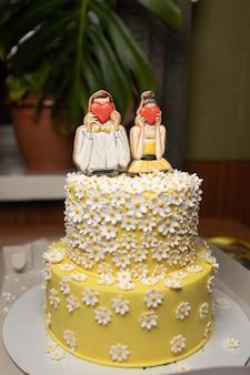 Lindo bolo amarelo festivo com um homem e uma mulher que cobrem seus rostos com corações