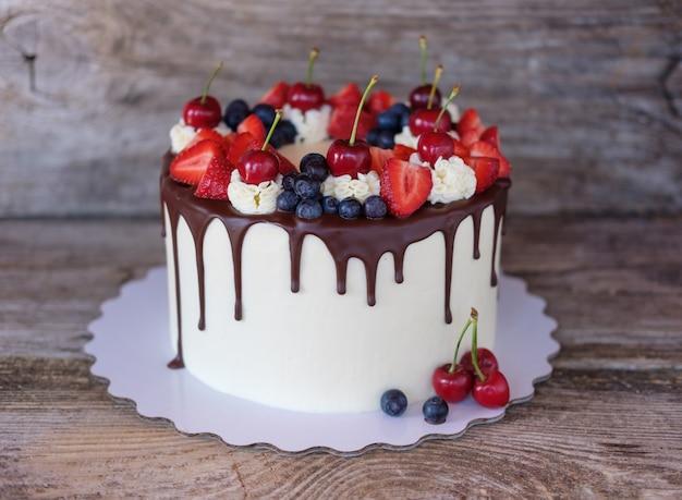Lindo bolo caseiro com cobertura de chocolate, morangos, cerejas e mirtilos na mesa de madeira