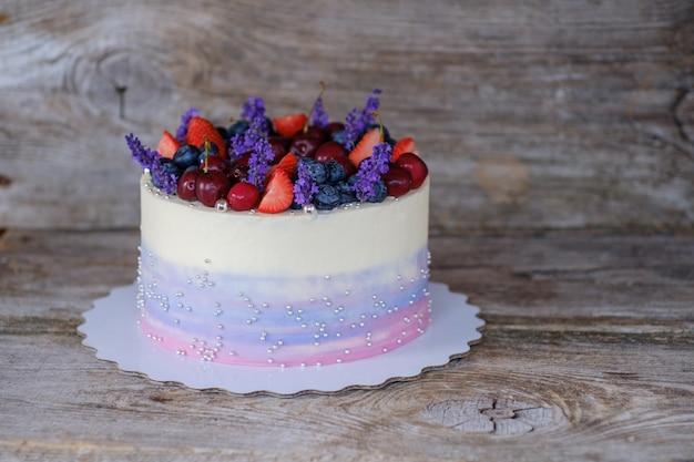 Lindo bolo caseiro com creme de queijo, cerejas, morangos e mirtilos, decorado com flores de lavanda