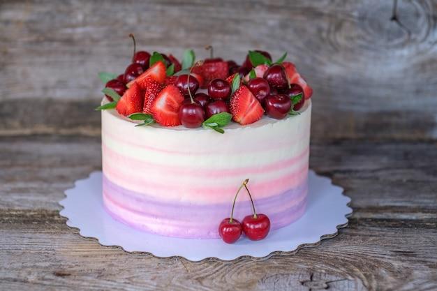 Lindo bolo caseiro com delicado creme roxo, rosa e branco e frutas de morango e cereja em uma mesa de madeira