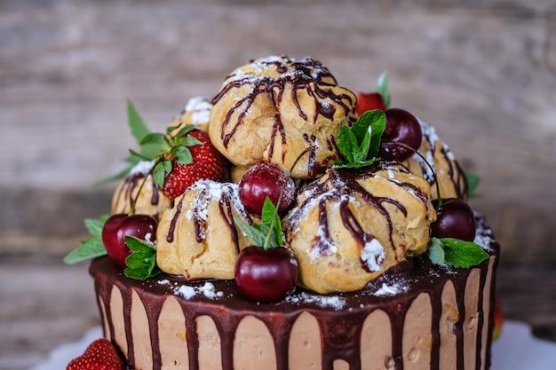 Lindo bolo caseiro com profiteroles, decorado com morangos e cerejas, em uma mesa de madeira
