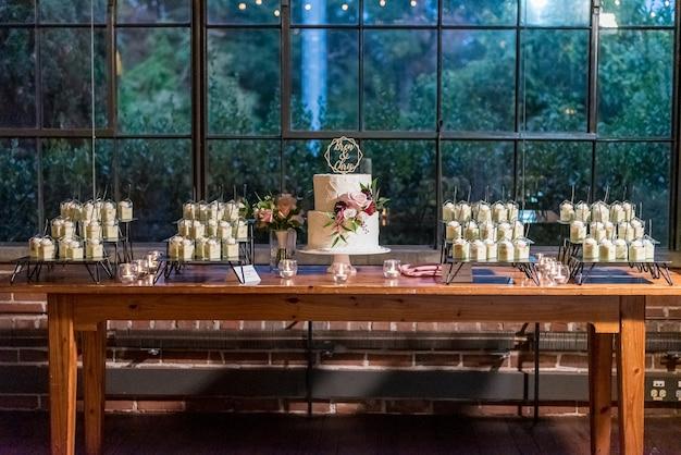 Lindo bolo de casamento branco com diferentes sobremesas em taças no conto