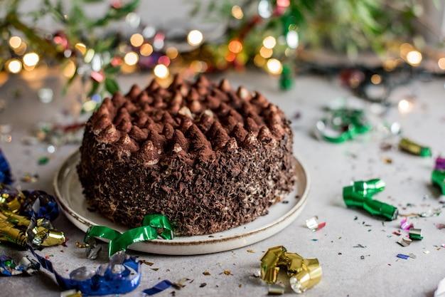 Lindo bolo de chocolate em cima da mesa entre confetes coloridos.
