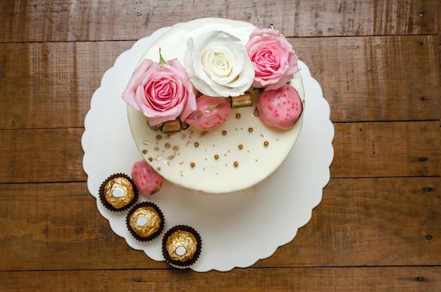 Lindo bolo decorado com rosas naturais e chocolates na mesa de madeira caseiro