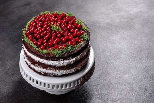Lindo bolo delicioso com bagas vermelhas brilhantes na mesa de natal