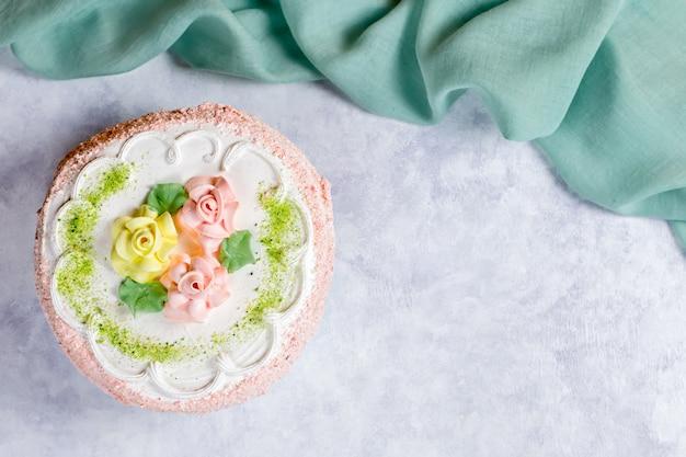 Lindo bolo delicioso decorado com flores em tons pastel na mesa de madeira com peônias, vista superior