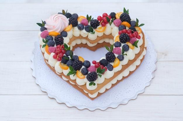 Lindo bolo em forma de coração com frutas frescas para o dia dos namorados na mesa de madeira branca