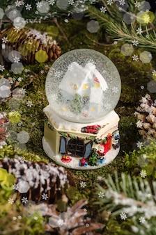 Lindo brinquedo de natal, um globo de neve com uma casa e uma árvore de natal dentro. ideia para presente e decoração de natal