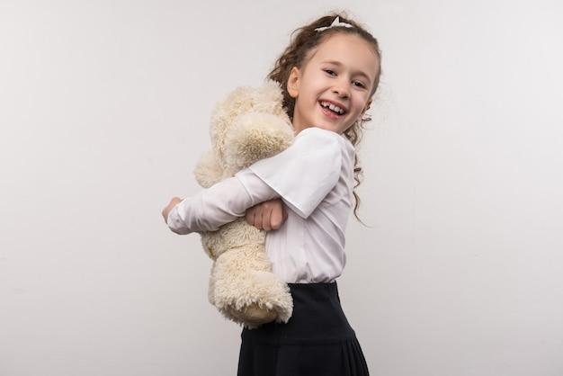 Lindo brinquedo. linda garota encantada abraçando seu urso enquanto se sente feliz