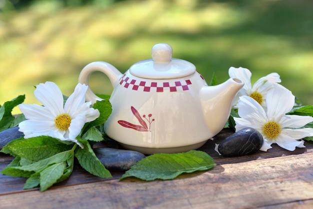 Lindo bule entre folhas de hortelã fresca e flores brancas em uma mesa de madeira no jardim