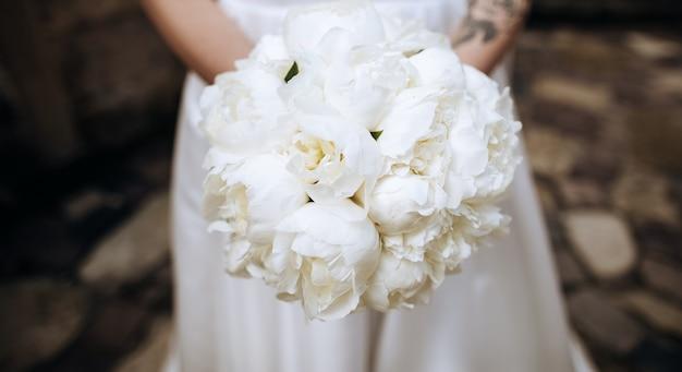 Lindo buquê branco de peônias nas mãos da noiva em um vestido branco